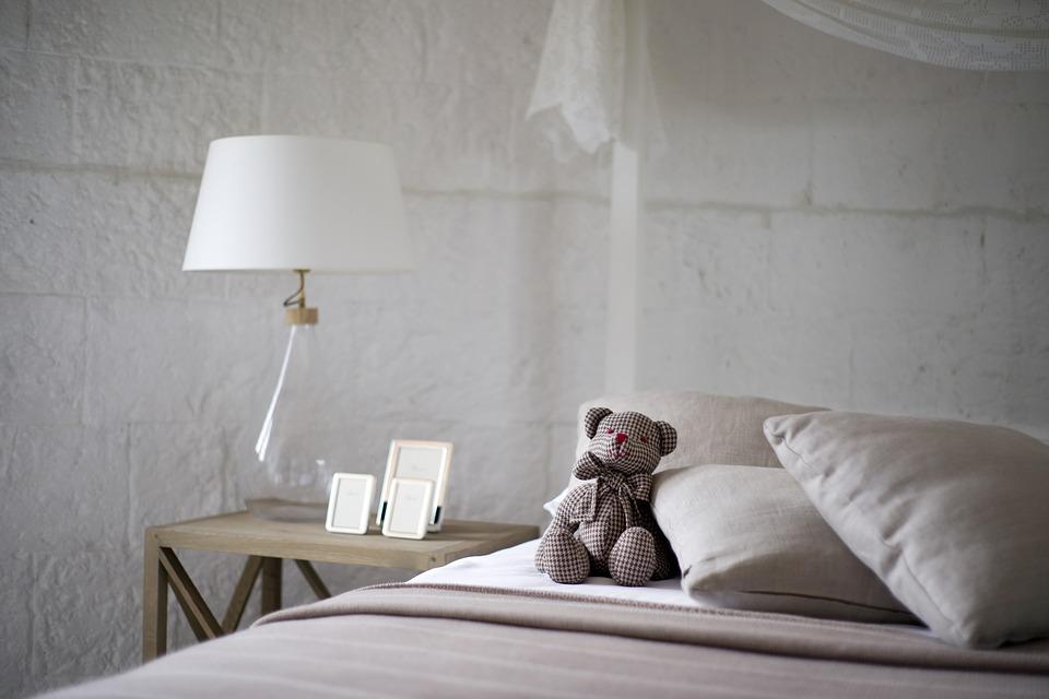 pluszowy miś w kratkę siedzący na łóżku