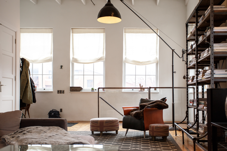 pomieszczenie z regałami i fotelem w stylu industrialnym