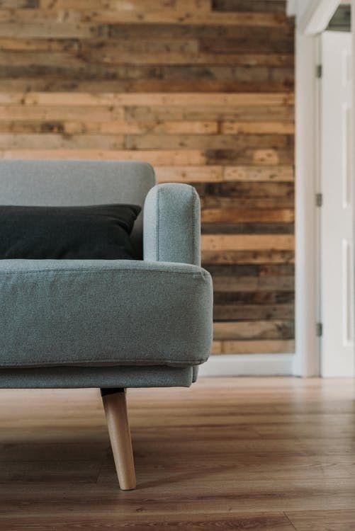 szara kanapa na tle naturalnego drewna