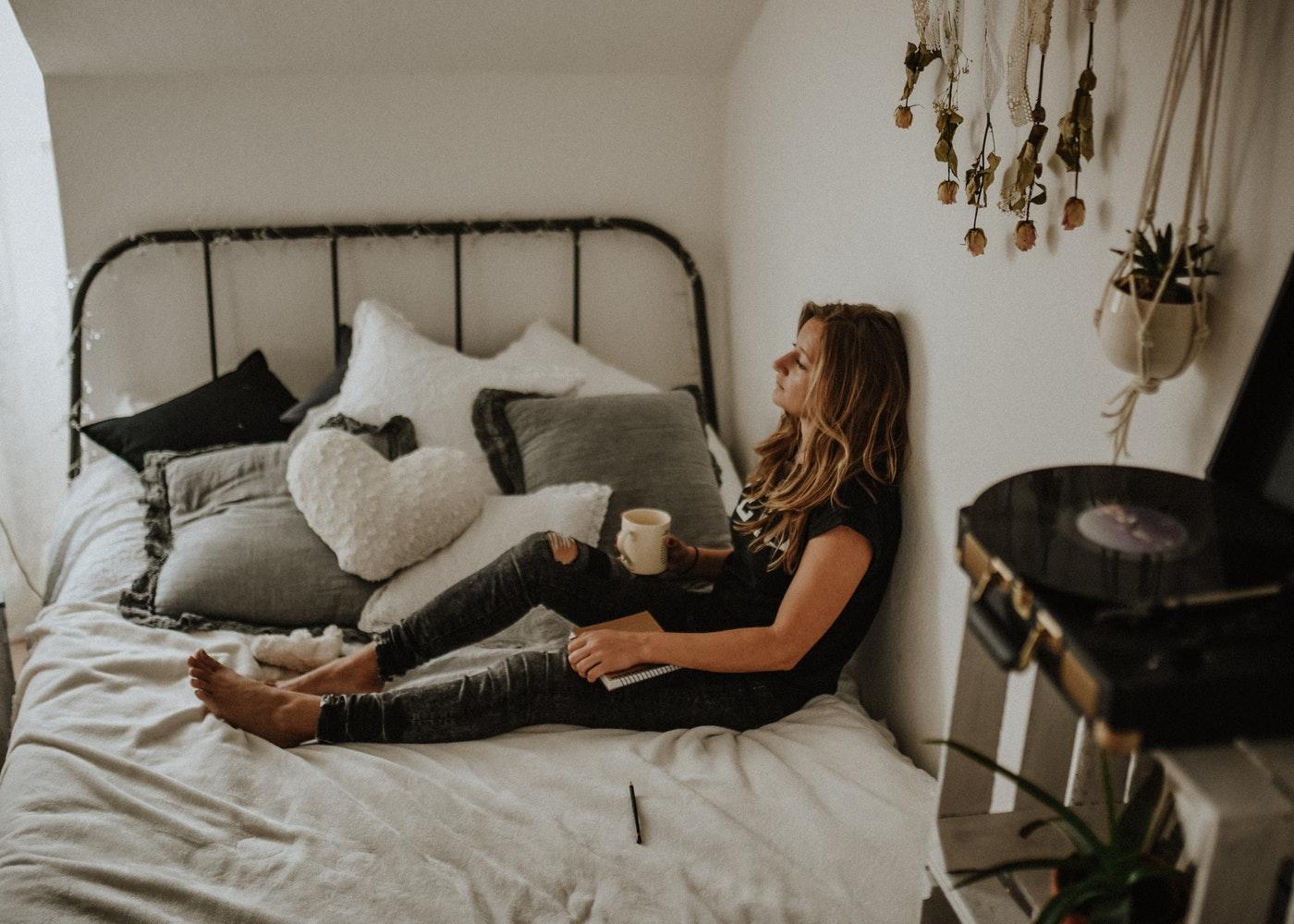 kobieta odpoczywająca na łóżku we wnętrzu w stylu etno